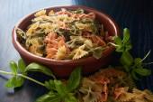 Schlaufenpasta, helle natürliche Farben, Basilikumgrün und, mit blauer Szene, zum Kochen vorbereitet