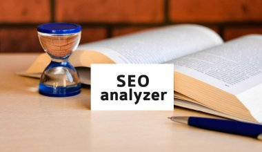 Seo analyzer business concept text on a white background with a hourglass and an open book