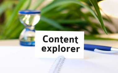 Content explorer seo business concept text on a white notebook and hourglass, blue pen, green flowers