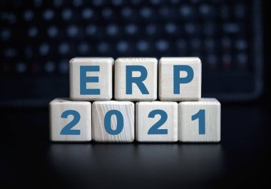 ERP - text in 2021 concept. Wooden cubes on a black keyboard