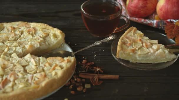Kousek domácího jablečného koláče Charlotte z červených a žlutých jablek. Zátiší na téma podzimu, sklizeň jablek a domácí dorty na tmavém dřevěném stole.