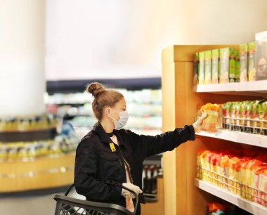 supermarket shopping, face mask and gloves,Woman choosing a dairy products at supermarket