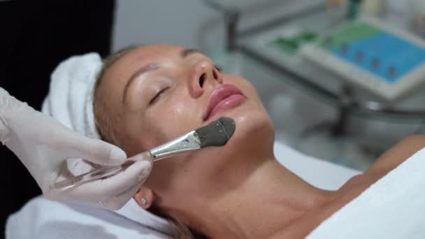 Kosmetikerin tragen Tonmaske mit Pinsel auf junge hübsche Frau Gesicht in Schönheitsklinik, Wellness-Salon. Kosmetikerin macht Schönheit Gesichtspflege Verfahren zu kaukasischen europäischen weiblichen