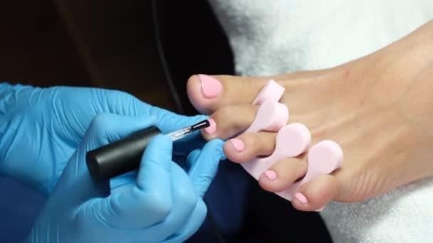 Salon Pediküre zu Hause. Fußpflege und Nagelpflege. Der Prozess der professionellen Pediküre. Meister in blauen Handschuhen tragen hellrosa Gel-Politur auf.