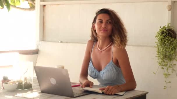 Hezká kavkazská žena s krátkými kudrnatými vlasy v romantických modrých šatech vzdálenost práce v létě venkovní kavárna s notebookem, mobilní telefon, notebook.