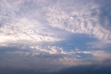 White cirrus clouds sprawled across the sky in front of a dark thunderous front