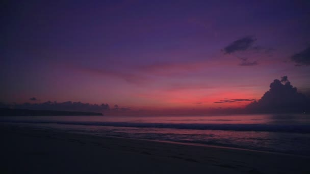Bright colorful sunset or sunrise at ocean with clouds at tropical beach