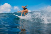 Surf woman at surfboard ride on wave. Woman in ocean during surfing. Surfer and ocean