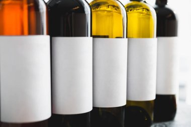Close view of row of wine bottles with white labels