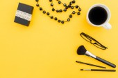 Fotografie Frame with paper box, glasses, cosmetics, bijouterie and accessories with cup of coffee on yellow background. Flat lay, top view.