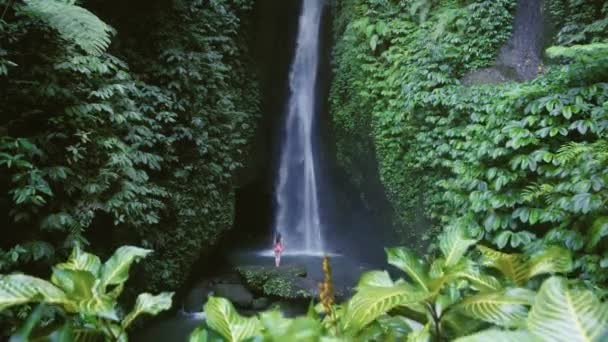 woman standing near huge waterfall in tropical forest, Bali, Indonesia