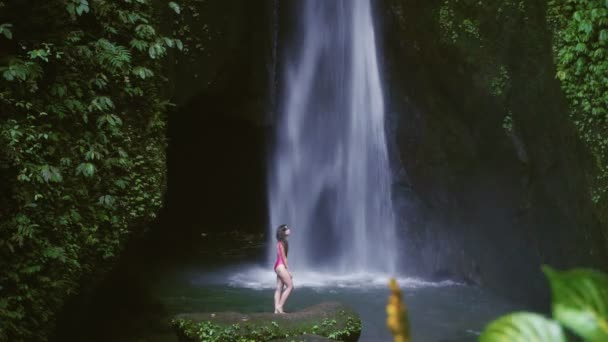 Woman in swimsuit relaxing at waterfall in Bali, Indonesia. Tropical forest and waterfall