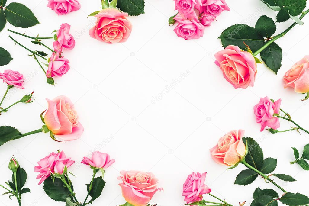 Round frame made of bright pink roses flowers on white background. Flat lay, top view. Pastel flowers