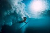 Fotografie Surfer girl with surfboard dive underwater with under big ocean wave.