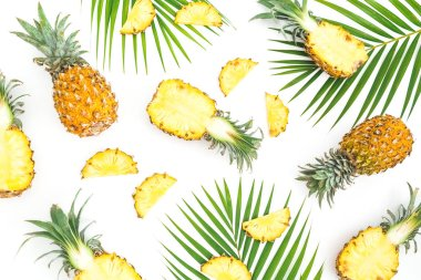 Tropical food pattern made of pineapple fruits with palm leaves on white background. Flat lay, top view.