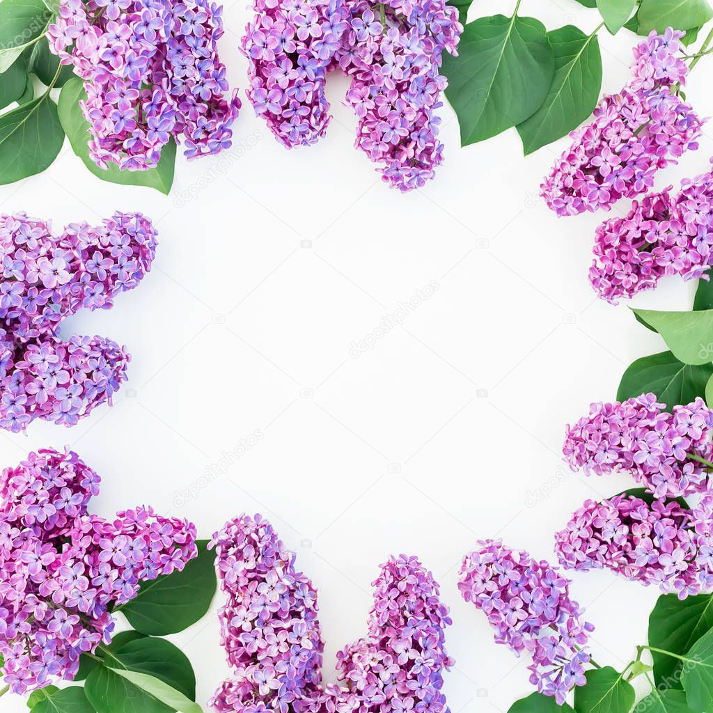 Floral round frame with purple lilac flowers and leaves on white background. Flat lay, top view