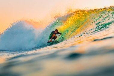 September 8, 2018. Bali, Indonesia. Surfer ride on barrel wave at warm sunset. Professional surfing in ocean, Bingin beach