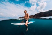 Surfer man with surfboard relaxing at line up in ocean
