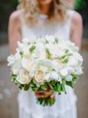 Fotografia Sposa in vestito bianco tiene un mazzo di fiori con i fiori delle Rose. Cerimonia e matrimonio