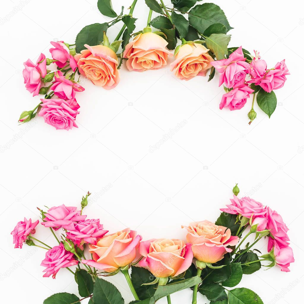 Floral frame of pink flowers and green leaves on white background. Flat lay, top view. Flower background