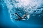 Surfermädchen mit Surfbrett tauchen unter Wasser mit Spaß unter der Welle.
