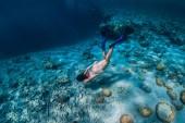 Fotografie Frau Freitaucher unter Wasser schwimmen im tropischen Ozean