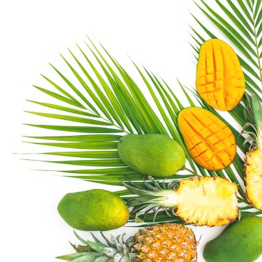 Tropical frame of pineapple and mango fruits with palm leaves on white background. Flat lay, top view.