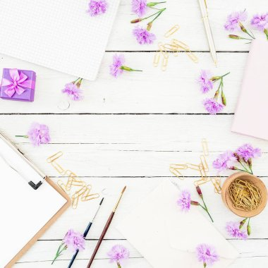 Freelancer workspace with clipboard, notebook, pink flowers and accessories on rustic wooden table. Flat lay, top view. stock vector
