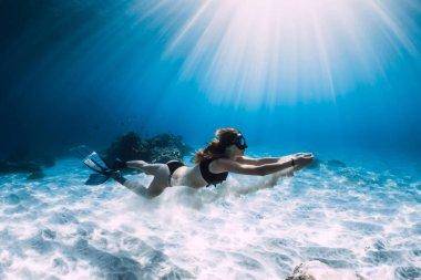 Kadın freediver yüzgeçleri ile kumlu alt üzerinde yüzmek. Serbest dalış sualtı Hawaii
