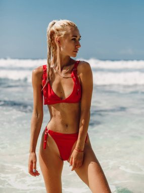 Attractive young woman in bikini relax at tropical beach in Bali. Model with ocean