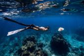 Fotografie Freitaucherin mit Flossen gleitet mit Meeresschildkröte im Wasser