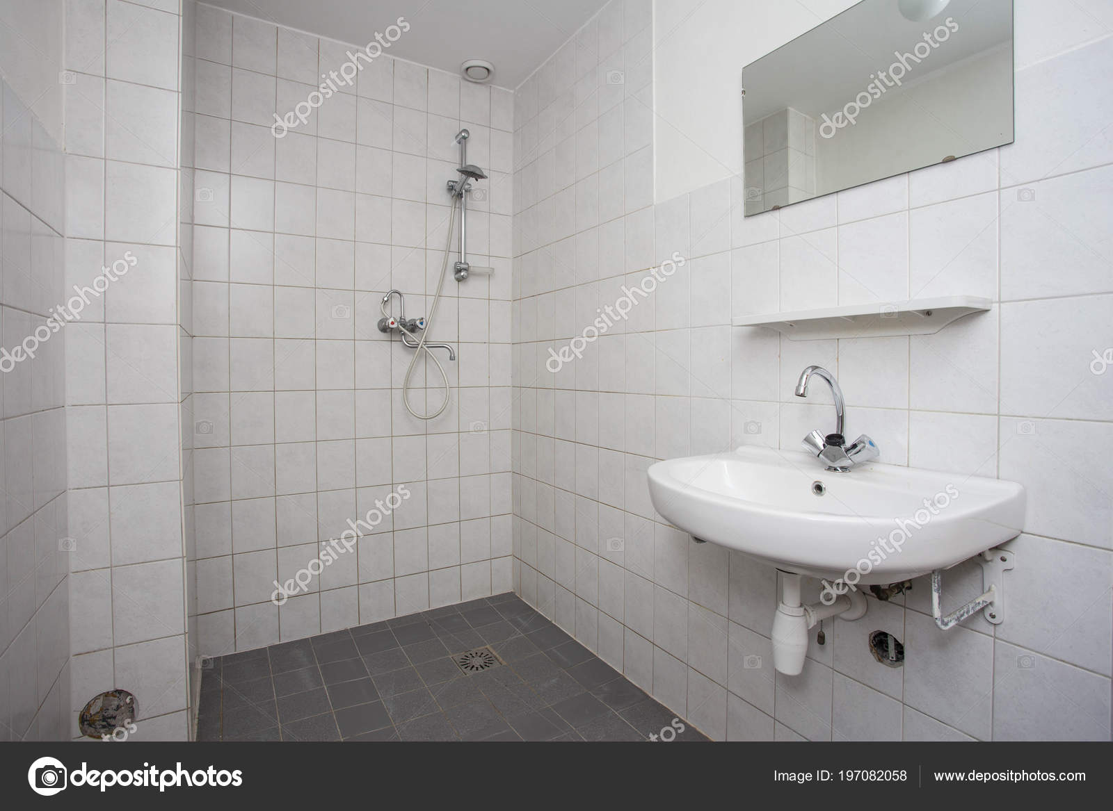 Simple, old clean bathroom with white tiled floor sink and shower ...