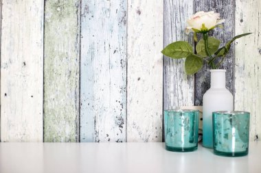 one colorful flower in white vase against wood wall with blue decoration