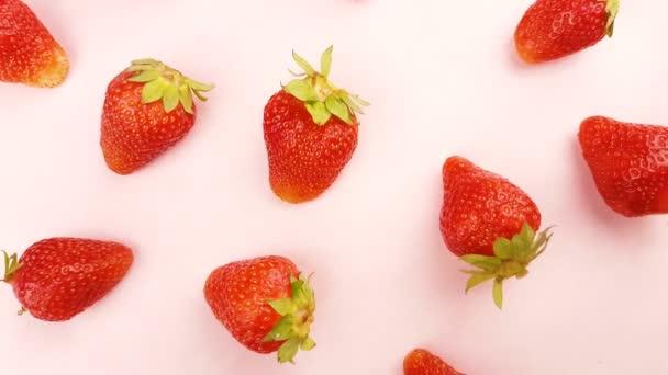 Červené čerstvé jahody rotující v pastelově růžové povrchu.