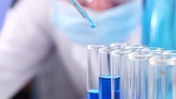 Vědec s pipetou v laboratorních kapka kapaliny ve zkumavce. Detailní záběr.