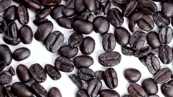 schwarze Kaffeebohnen rotieren auf weißer Oberfläche aus nächster Nähe.