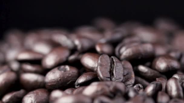 schwarze Kaffeebohnen rotieren auf schwarzer Oberfläche. Nahaufnahme.