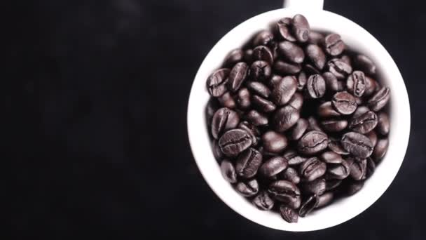 Dark coffee beans in white cup rotating on black surface.