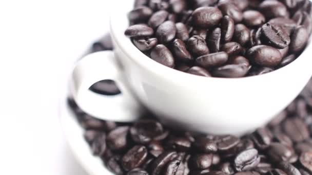 Black coffee beans in cup and plate rotating on white backgroun. Close up.