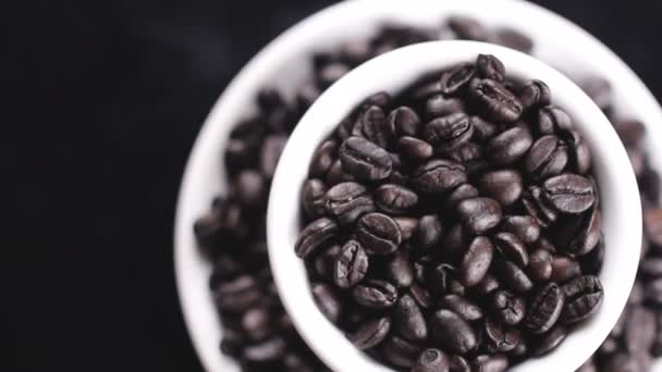 Black coffee beans in white cap and plate rotating on dark background.