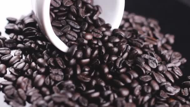 dunkle Kaffeebohnen in weißer Tasse rotierend auf schwarzer Oberfläche.