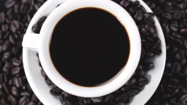 Black coffee in white cup on plate with coffee beans rotating on dark surface. Close up.