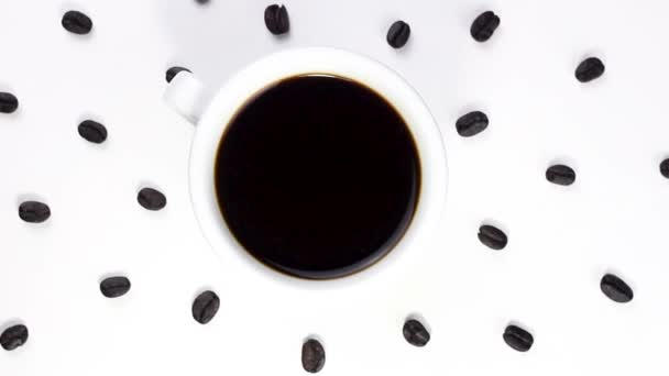 Black coffee in white cup with coffee beans rotating on white surface. Close up.