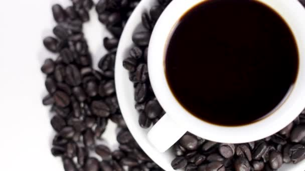 Black coffee in white cup on plate with coffee beans rotating on white background. Close up.