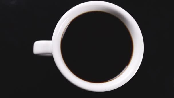 Black coffee in white cup rotating on dark surface.