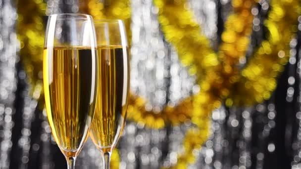 zwei Gläser Champagner mit weihnachtlicher Silber- und Goldlametta-Dekoration auf Hintergrund.