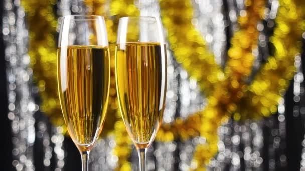 Dvě sklenice šampaňského točivých vánoční stříbrné a zlaté pozlátko dekorace na pozadí.