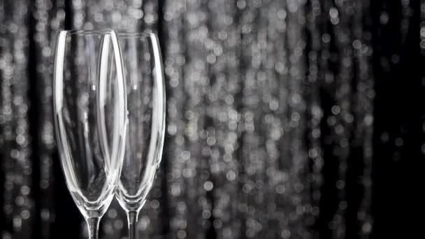 Detailní záběr dvou sklenic na šampaňské nad dovolenou pozlátko bokeh blikající pozadí.