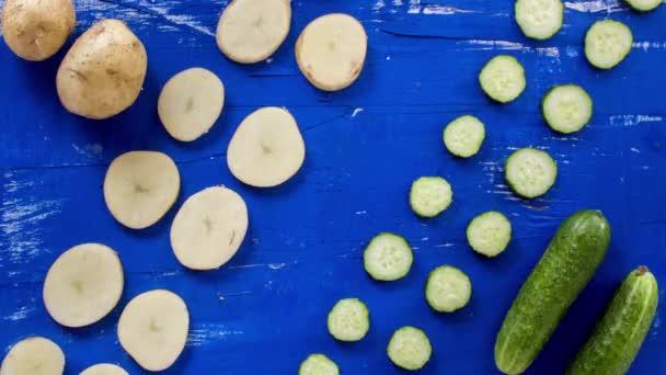 Abstraktní zelenina na modrém dřevěném povrchu zastaví pohybové záběry. 4k animovaná švotele