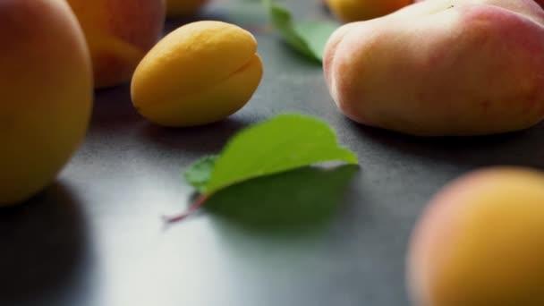 Szép finom friss szeletelt sárgabarack zöld fa elhagyja a sötét textúra felületén. Nyári gyümölcsök. 4k.